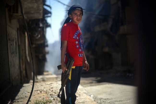 "A Syrian boy holds an AK-47 assault rifle in the majority-Kurdish Sheikh Maqsud district of the northern Syrian city of Aleppo. US intelligence agencies determined with ""some degree of varying confidence"" that chemical weapons have been used in Syria as of April 25, 2013. (DIMITAR DILKOFF/AFP/Getty Images)"
