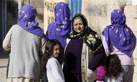 Turkish women stand near their homes in the Turkish border town of Ceylanpinar, Sanliurfa province