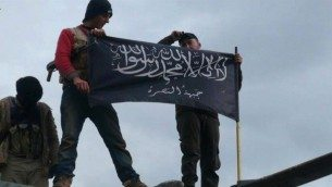 Al-Nusra Front activist wave their brigade flag atop a Syrian air force helicopter, at Taftanaz air base, captured by the rebels in Idlib province, northern Syria, January 2013 (photo credit: AP/Edlib News Network ENN, File)